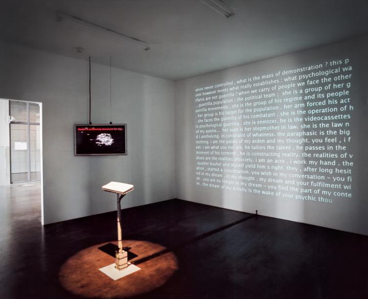 In einem Raum steht eine Tastatur. An einer Wand hängt ein Bildschirm, auf eine andere Wand wird Text projiziert.
