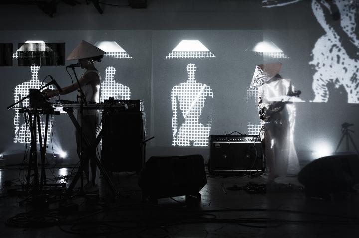 Das Duo group A performt live auf der Bühne, im Hintergrund Visuals aus abstrakten Figuren mit traditionellen asiatischen Kegelhüten