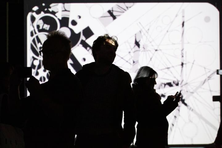 Photo of people in front of a projection screen with an abstract video in black and white - an impression of the exhibition »bauhaus.film.expanded« at the ZKM Karlsruhe.