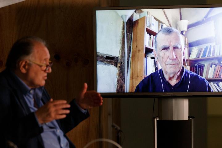 Peter Weibel sitzt vor einem großen Bildschirm auf dem Bruno Latour zu sehen ist.