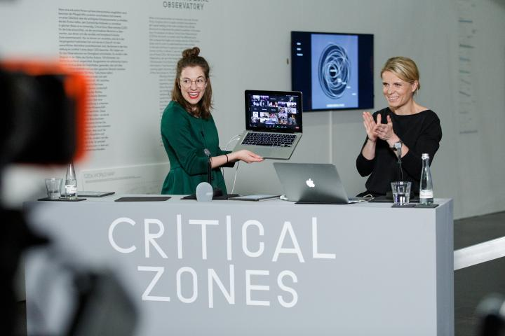 Two women stand behind a desk. One woman is holding an open laptop, beaming with joy.