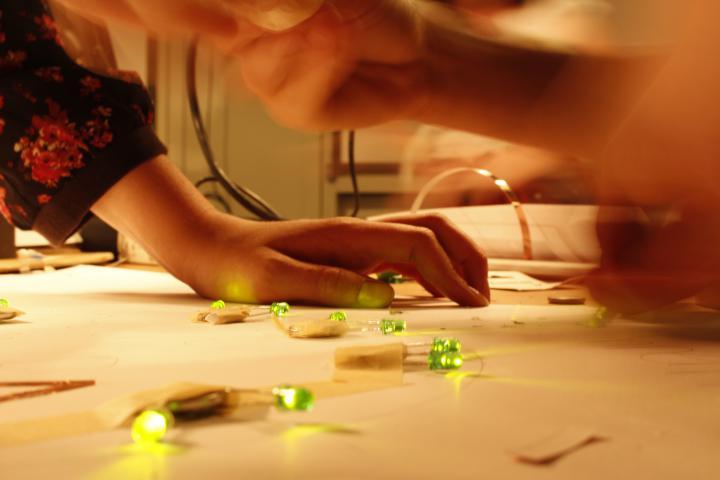 Man sieht eine Hand, die sich auf den Tisch aufstützt und auf dem - auf Papier geklebte - grüne LEDs leuchten.