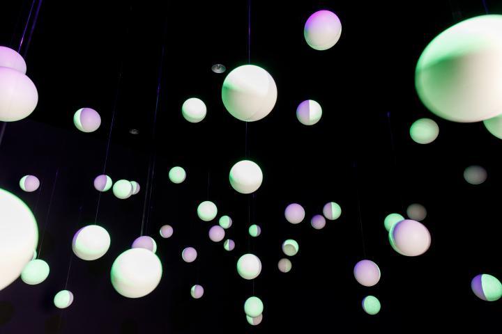 Weiße Styroporkugeln  hängen in einem schwarzen Raum, die Kugeln sind mit fluoreszierender Farbe bemalt und werden angeleuchtet.
