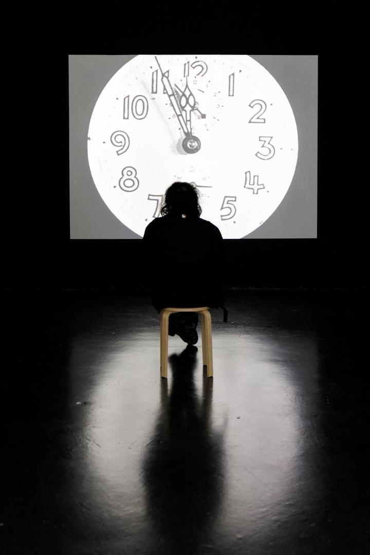 The photo shows the silhouette of a person watching a black and white film on a large screen. On the screen, an analogue clock strikes twelve. The light of the screen falls a round blurred light on the floor.