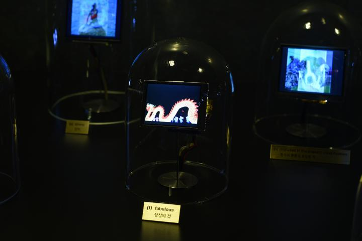 The photo shows a glass bell with a small screen. On this one you can see a dragon-like creature.