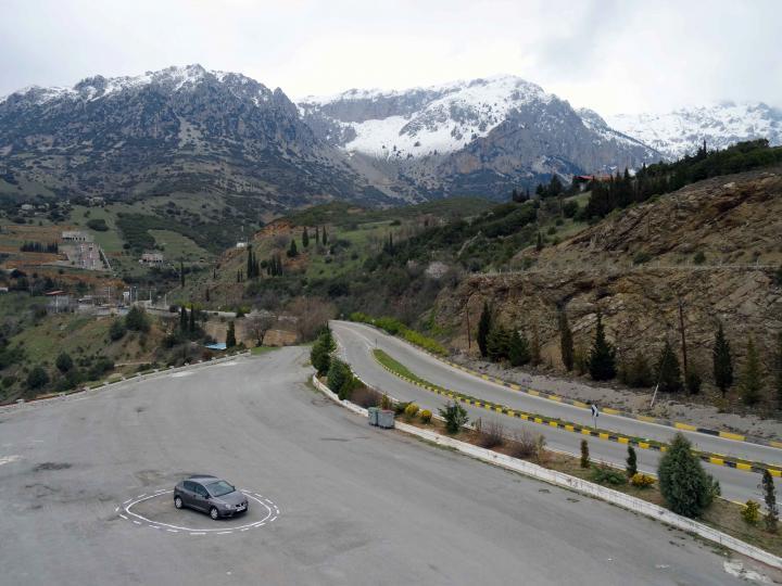 Ein selbstfahrendes Auto steht auf einem leeren Parkplatz in einem Kreis aus einer durchgezogenen und einer gestrichelten weißen Linie.