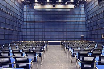 Bild des ZKM Medientheaters mit Reihenbestuhlung und Bühne. Moderne Architektur in blauem Grundton.
