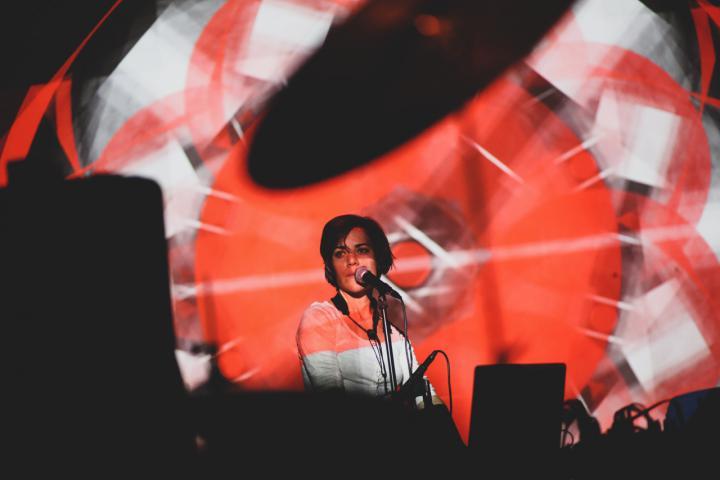 Eine Frau am Mikrofon, vor ihr rot-weiße Lichtprojektionen.