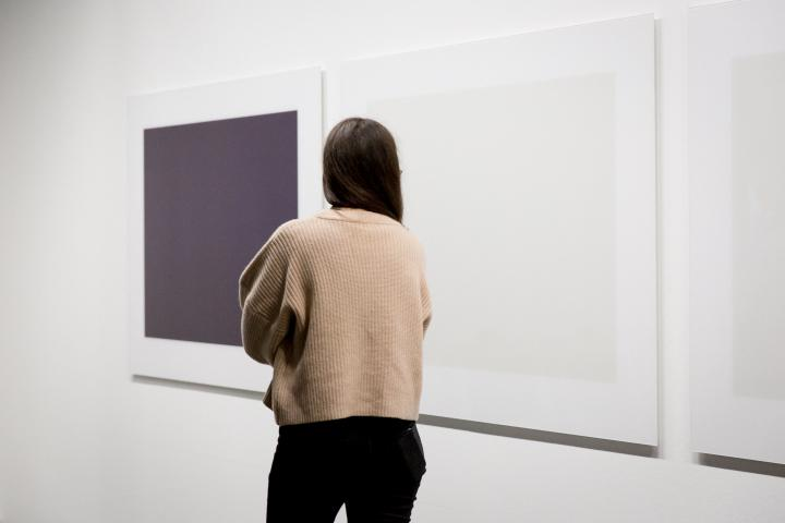 A Woman stands in front of an artwork