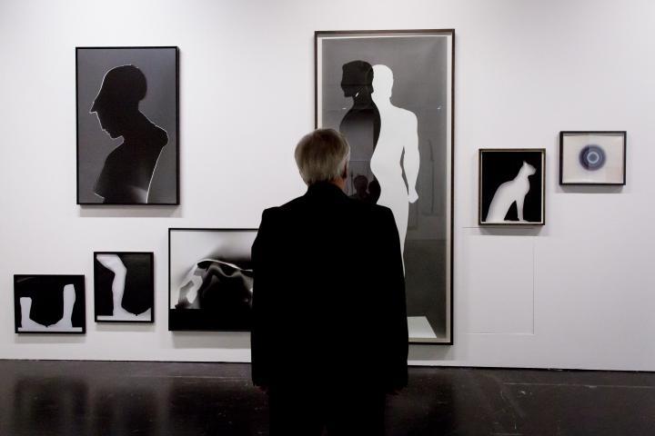 Ein Mann steht vor verschiedenen Bildern in Schwarz-Weiß