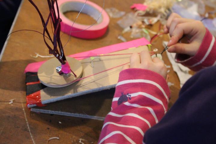 Ein Kind arbeitet an einer Automaten-Konstruktion, an die es ein Rad angebracht hat, das durch ein Gummiband und einen kleinen Motor zum Drehen gebracht werden soll.