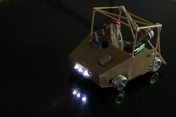"""Eine """"Maker""""-Fantasiefigur ist in einem Auto sitzend zu sehen"""