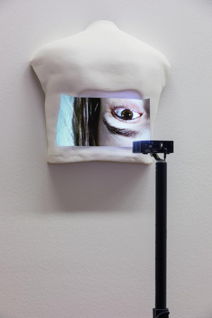 You can see a white object hanging on the wall. On the object is a picture of a section of a woman's face.