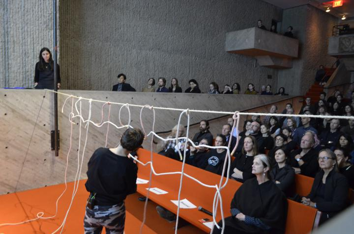 Das Foto zeigt einen brutalistischen Vortragssaal mit Blick auf das Publikum. Die Bühen ist angeschnitten. ein großes Publikum schaut der Performerin zu, wie sie ein Netz aus Seilen bildet.