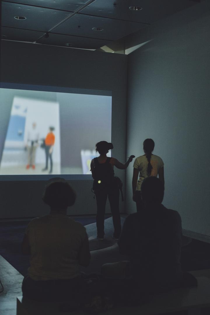 Das Bild zeigt eine Besucherin, die eine VR-Brille trägt