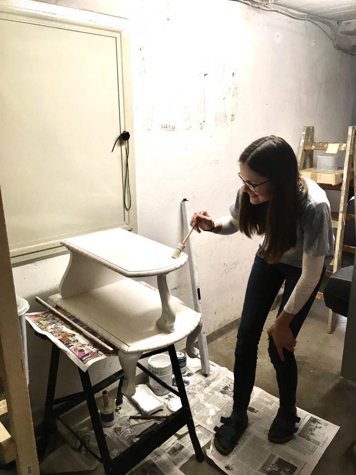 Das Bild zeigt eine Schülerin, die mit einem Pinsel in einem Innenraum ein Holzobjekt mit weißer Farbe streicht. Das Bild ist im Rahmen der Kulturakademie Baden-Württemberg 2020/21 entstanden.