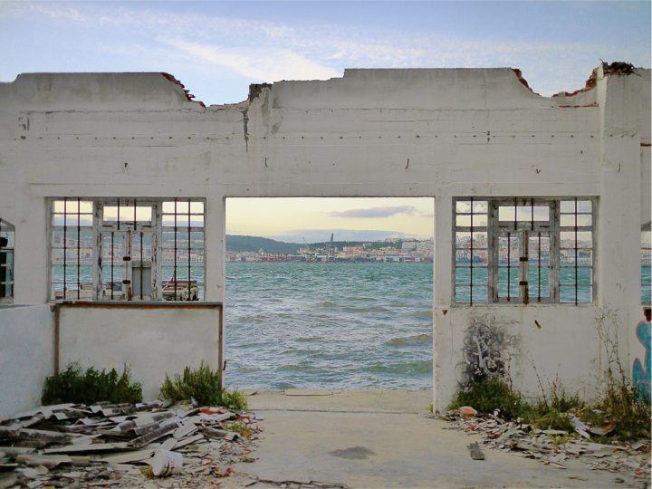 The picture shows a house ruin, through whose open doors and windows you can see the sea and a city behind it.