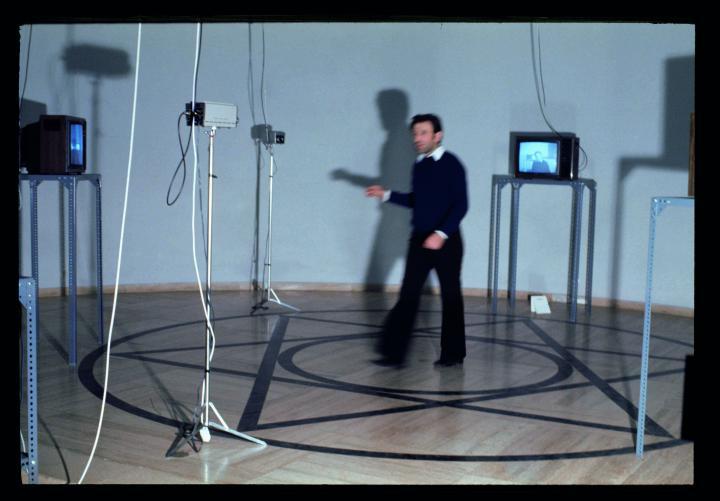 Ein Mann steht in einem Pentagramm umgeben von Monitoren und Kameras. Das Foto zeigt Peter Weibel im Rahmen der Ausstellung »respektive Peter Weibel«.