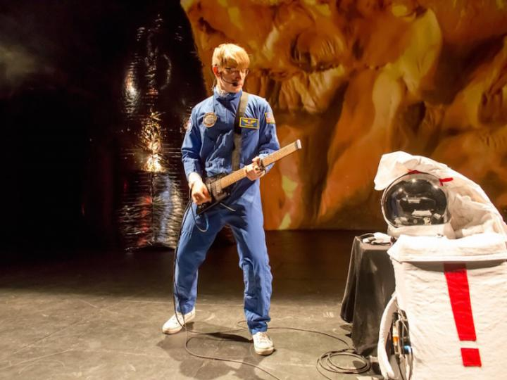Zu sehen ist ein junger Mann in einem blauem Astronauten Anzug und einer Gitarre in der Hand.