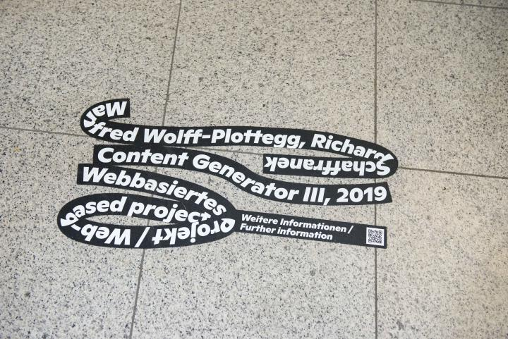 """The black loop of the exhibition """"Seasons of Media Arts"""" sticks to a tiled floor, with white writing over the artwork Content Generator III."""