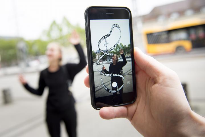 Im Vordergrund sieht man ein Handy auf dessen Display ein App-Kunstwerk zu sehen ist. Die virtuelle »Seasons of Media Arts« Schlaufe und eine blonde Frau, die die Enden der Schlaufe versucht zusammenzuhalten.