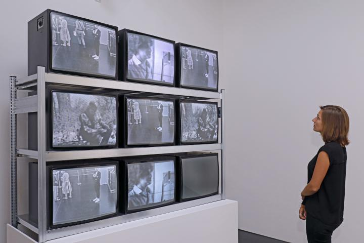 Visitor in front of an installation consisting of nine TV screens