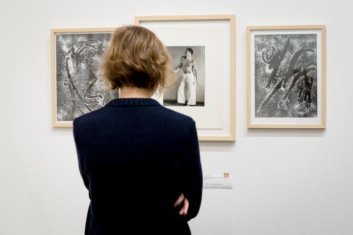 Eine Frau betrachtet verschiedene Fotografien