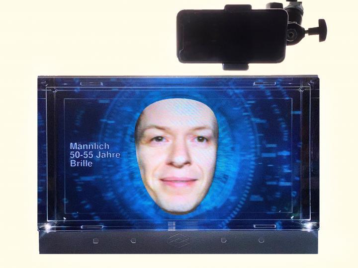 Ein kleiner Bildschirm zeigt ein Gesicht vor einem blauem Hintergrund.