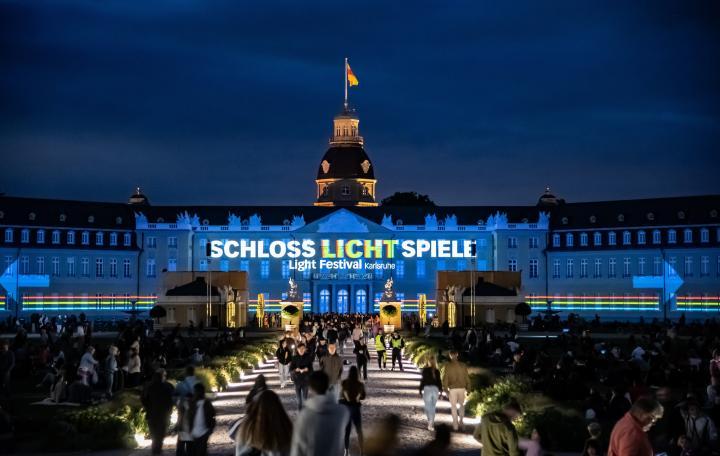 Foto eines bunten Projection Mappings bei Nacht auf dem barocken Karlsruher Schloss. Zu sehen ist der Text »Schlosslichtspiele«