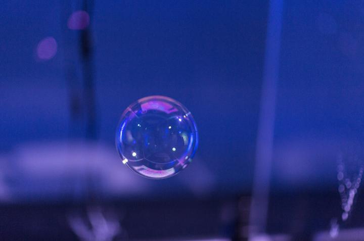 Eine Seifenblase vor einem violetten, dunklen Hintergrund.
