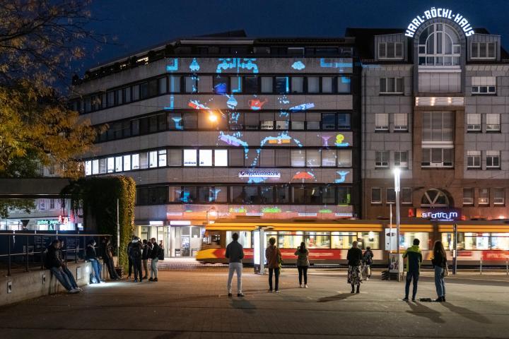 ge Projektion zeigt einzelne fabrige Elemente verteilt auf einer Gebäudefassade: ein langer Wasserhahn, eine Wasserpistole mit Trichter, ein Regenschirm.