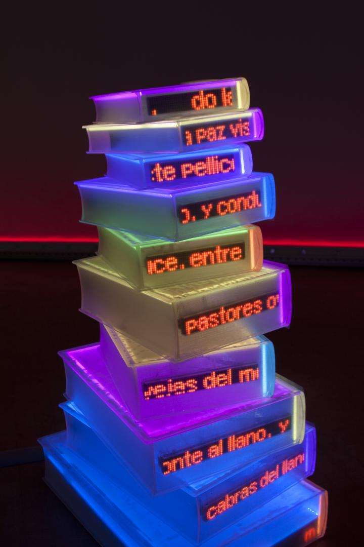 Bunt leuchtende Bücher sind zu einer Skulptur aufgestapelt.