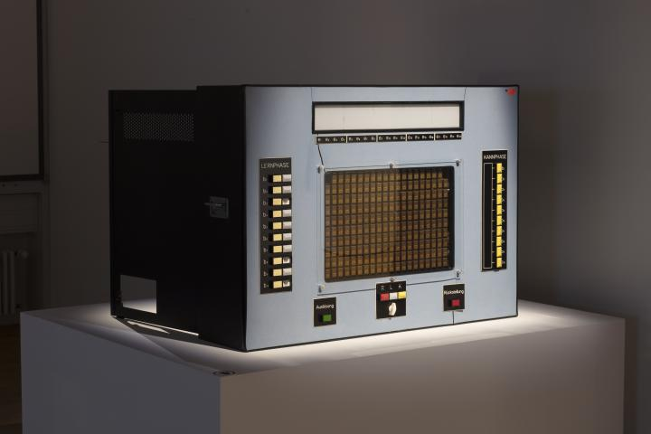 A learning computer from the 60s, rectangular, in grey and with many buttons.