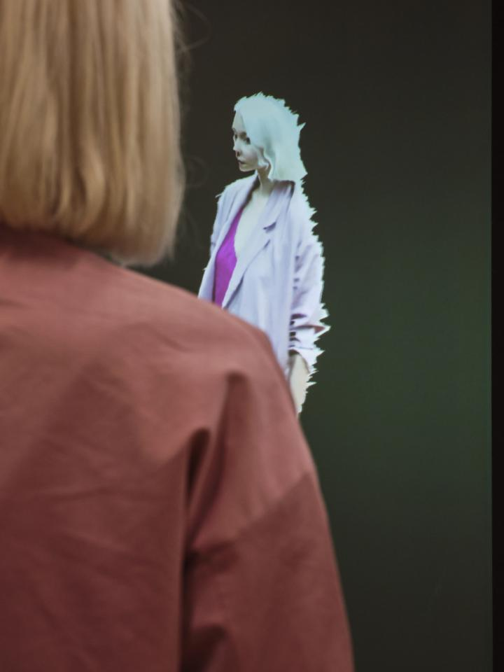 In the foreground of the photo you can see a light blonde woman with short hair and a pink jacket. In front of her she is reproduced as an avatar on a screen. The visitor faces her digital code.