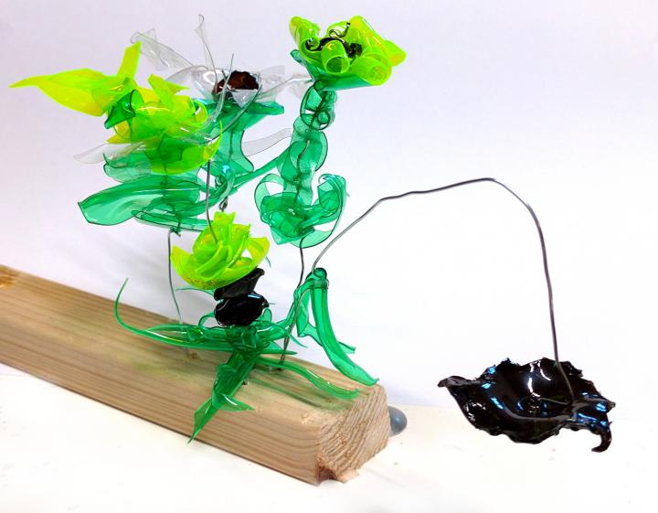 Auf einem Vierkantholz stecken an Draht sich emporrankende Plastikblumen in fantastischen Formen. Sie wurden aus grünen, gelben klaren und schwarzen PET-Flaschen hergestellt.